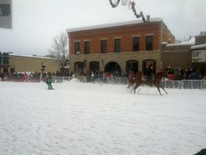 horse pulling a child on skis down a street in front of a crowd